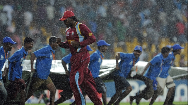 West Indies batsman Chris Gayle runs for cover as ground staff pull a tarp over the pitch as rain stops play