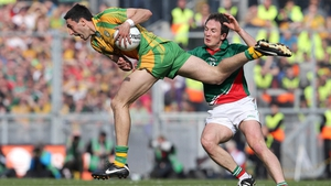 Rory Kavanagh bursts through the tackle of Alan Dillon