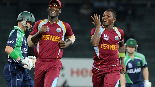William Porterfield walks away after being bowled first ball by Fidel Edwards (right). Fellow Windies bowler Darren Sammy joins in the celebrations