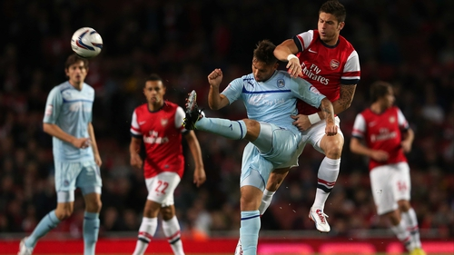 Olivier Giroud of Arsenal challenges Coventry's James Bailey