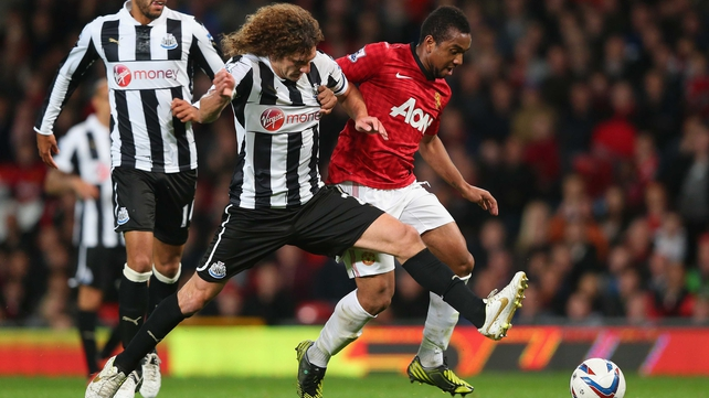 Manchester United's Anderson holds off the challenge of Fabricio Coloccini