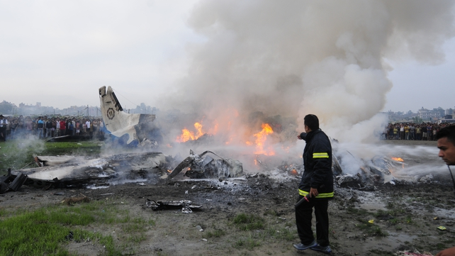Firemen battle flames from the wreckage of the Sita Air Dornier plane crash in Manohara, near Kathmandu