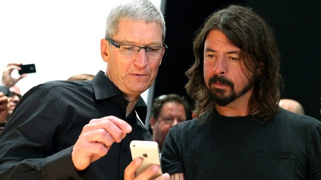 Apple CEO Tim Cook shows musician Dave Grohl the iPhone 5