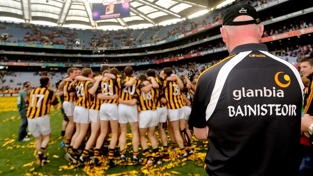 Brian Cody watches on as his players celebrate victory in the 2