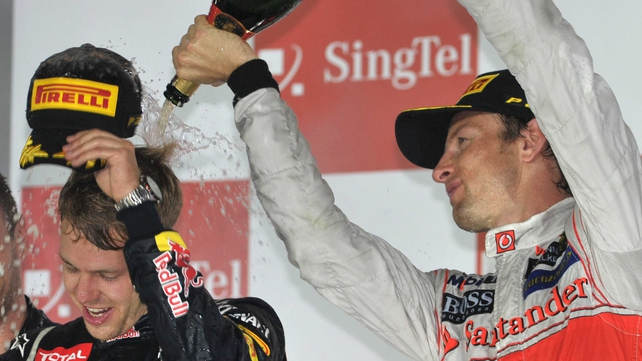 Jenson Button (R) pours champagne over Sebastian Vettel in Singapore
