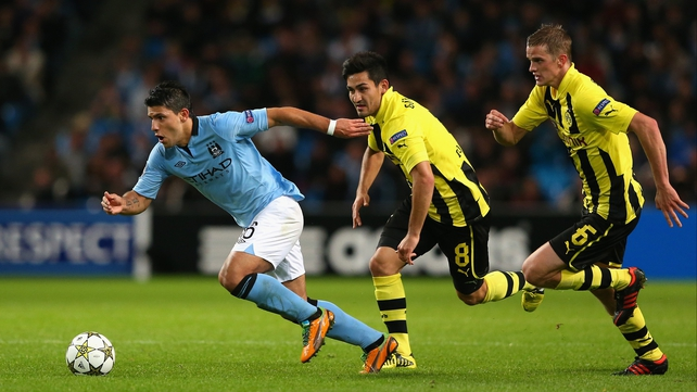 Sergio Aguero of Manchester City looks to evade Ilkay Gundogan and Sven Bender (r) of Borussia Dortmund