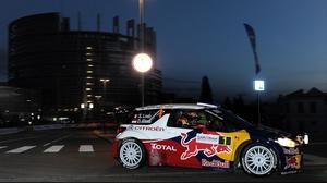 Sebastien Loeb and co-driver Daniel Elena steer their Citroen DS3 WRC in front of the European Parliament