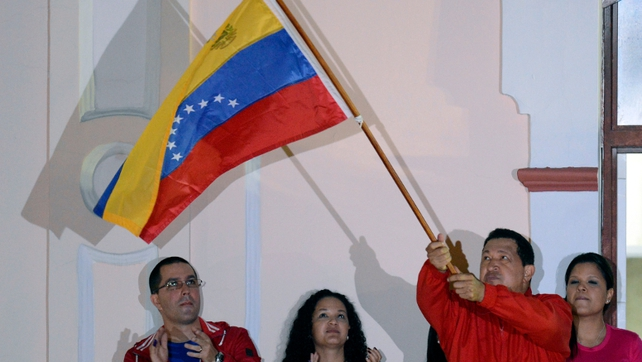 Hugo Chavez waves the Venezuelan flag on hearing the news about his fourth term