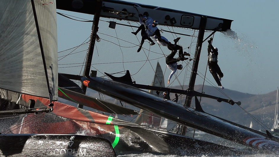 Oracle Team USA flips over during a fleet race in the America's Cup World Series in San Francisco, California
