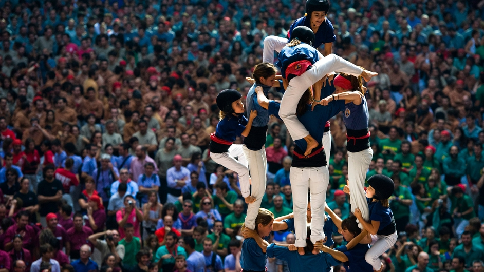 Members of the Colla 'Caprogossos de Mataro' climb up as they construct a human tower during the Tarragona Castells comptetion in Spain