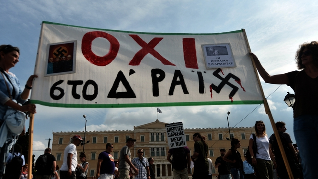 Protesters hold a banner reading 'No to the Fourth Reich' outside the parliament in Athens