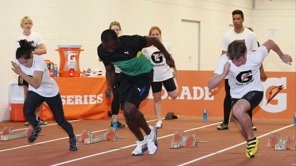 Usain Bolt practices the starting blocks with New Zealand sprinters Rochelle Coster and Joseph Millar