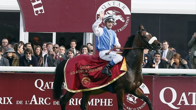 French jockey Olivier Peslier celebrates on Solemia after winning the Prix de l'Arc de Triomphe