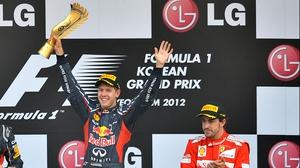 Sebastian Vettel (l) celebrates on the podium alongside third-placed Fernando Alonso