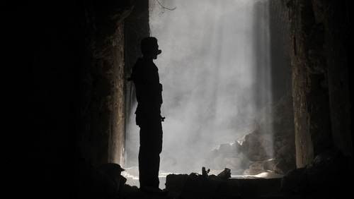 A Syrian rebel takes position during clashes with regime forces in Aleppo
