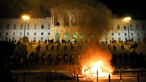 A fire burns as police guard the parliament building in Lisbon