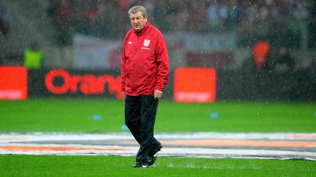 Roy Hodgson walks a soggy pitch in Warsaw