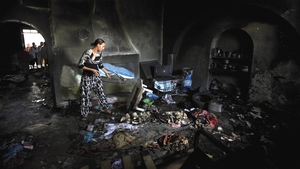 A woman tries to salvage items from the burnt-out Saida Manoubia shrine in the western La Manouba suburb of Tunis