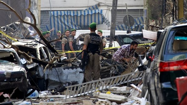 Police comb through the wreckage following yesterday's car bomb explosion in central Beirut