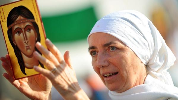 A mass-goer hold a portrait of Kateri Tekakwitha