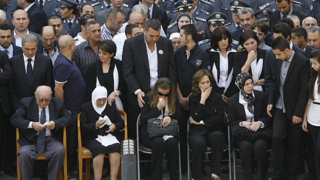 The wife (C) of Wissam al-Hassan, grieves during a ceremony outside ISF headquarters ahead of her husband's funeral