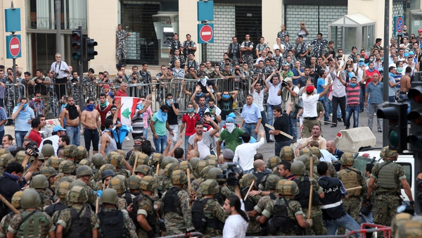 Protesters face off with Lebanese security forces as they try to storm the Government Palace in Beirut