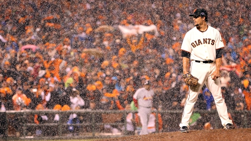 Javier Lopez of the San Francisco Giants pitches in the rain towards the end of the  ninth inning