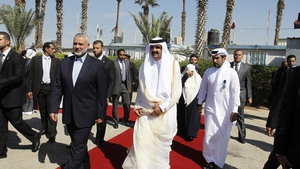 Qatari Emir Sheikh Hamad bin Khalifa al-Thani (r) walks alongside Gaza's Hamas prime minister Ismail Haniyeh (l) during a welcome ceremony at the Rafah border crossing with Egypt