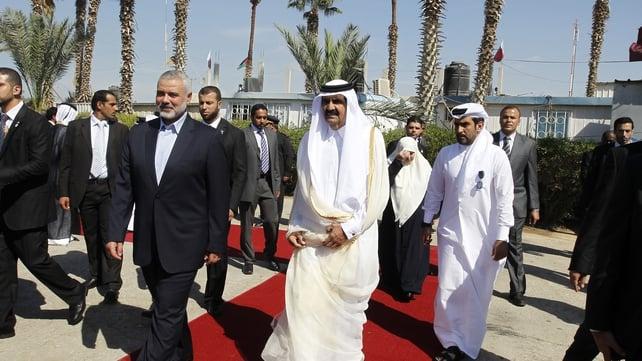 Qatari Emir Sheikh Hamad bin Khalifa al-Thani (r) walks alongside Gaza's Hamas prime minister Ismail Haniyeh (l) during a welcome ceremony at the Rafah border crossing with Egypt