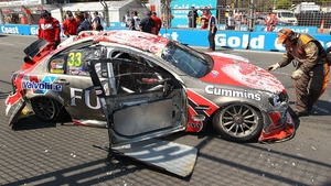 Ricky Taylor looks on after his Fujitsu Racing GRM Holden car lies on the track after a rollover in Australia