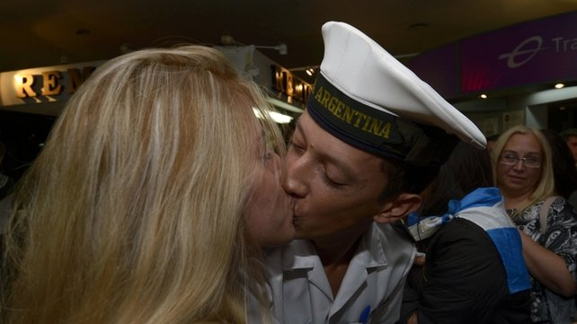 A crew member of the Argentine frigate ARA Libertad kisses a woman upon his arrival in Ezeiza's International airport in Buenos Aires