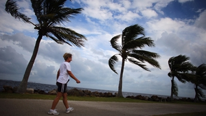 A woman walks along the ocean as blustery winds blow through the palm trees in Miami, Florida