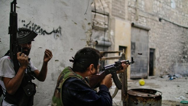 Members of the Free Syria Army fire towards regime loyalist soldiers during a battle in the northern city of Aleppo