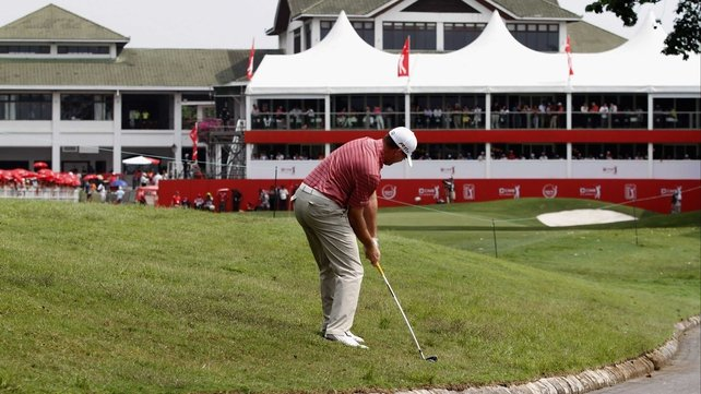 Robert Garrigus plays an approach shot towards the 18th hole