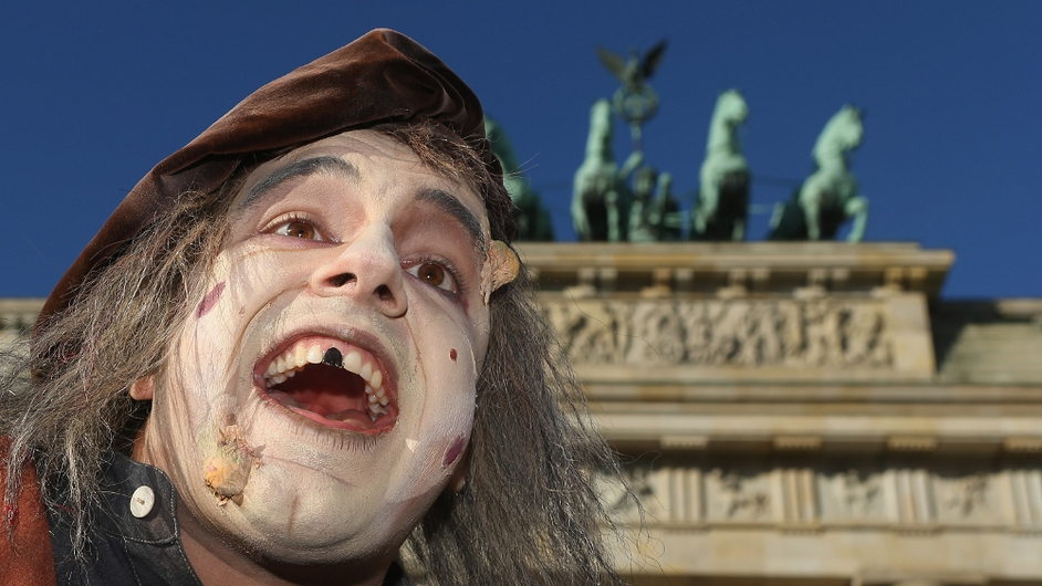 An actor pretending to be a zombie arrives at the Brandenburg Gate during a small event to promote the opening of Berlin Dungeon