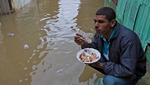 A man eats outside of his flooded house at La Barquita neighborhood Santo Domingo, Dominican Republic