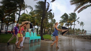 Dutch tourists are buffeted by high winds of the outer bands of Hurricane Sandy as they walk to a beach in Florida