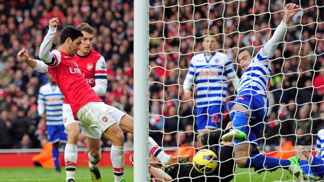 Arsenal's Mikel Arteta pokes the ball past Ryan Nelsen of QPR