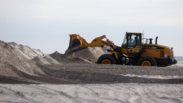 A bulldozer moves sand to help protect the shoreline in Long Beach, New York