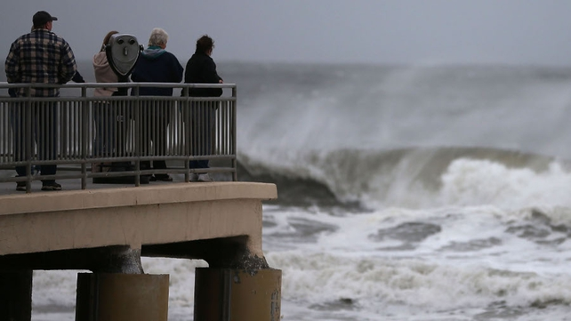 People stand on the Ocean City Music Pier watching heavy surf caused by Hurricane Sandy, in Ocean City, New Jersey