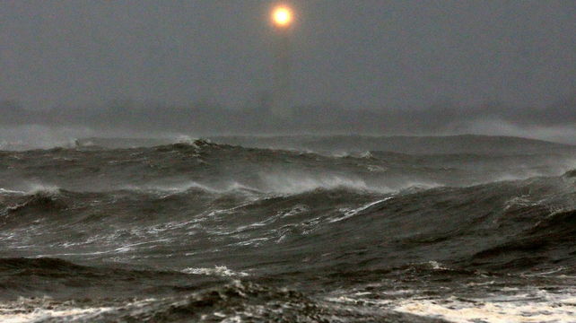 The Cape May Lighthouse can be seen as heavy surf pounds the shoreline in Cape May, New Jersey