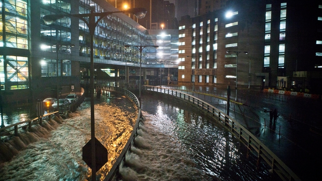 Water rushes into the Carey Tunnel in the Financial District of New York. All bus, subway and commuter rail services are closed