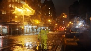 A Con Edison worker walks through the flood waters on the corner of 33rd Street and 1st Street in Manhattan