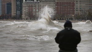 A man watches the waves crash against the shoreline of Lake Michigan in Chicago