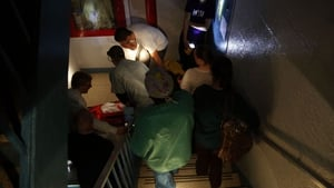 Hospital workers evacuate a patient from NYU Langone Medical Center after the blackout