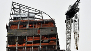 A construction crane dangles from a luxury high-rise building in midtown Manhattan after it collapsed in high winds