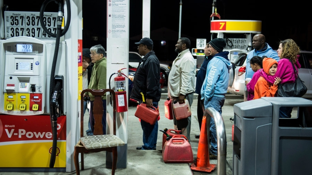 People wait in line to fill containers with fuel at a gas station in Edison, New Jersey