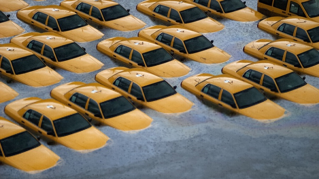 Dozens of yellow cabs in Hoboken, submerged in murky water