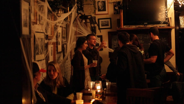 People gather inside Dorian Gray Tap and Grill during a power outage in the East Village neighbourhood of New York City