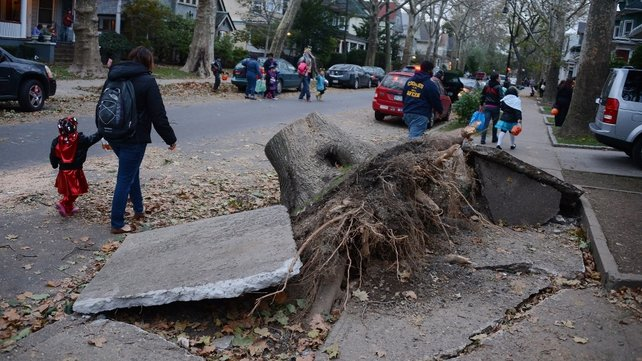 Halloween 'trick-or-treaters' pass some of the wreckage in a Brooklyn neighbourhood